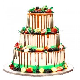 Белый свадебный торт, политый темным шоколадом и украшенный ассорти из фруктов и ягод
