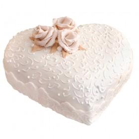 Белый одноярусный свадебный торт в форме сердца , украшенный цветами