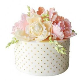 Белый одноярусный свадебный торт, украшенный бусинками и множеством цветов
