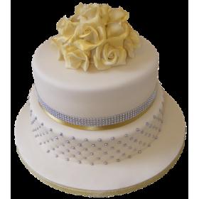Белый двухъярусный свадебный торт с цветами на верхнем ярусе