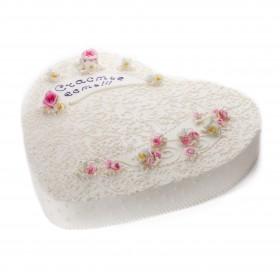 Торт праздничный в форме сердца покрыт белым кремом декорирован цветами роз