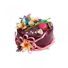 Праздничный торт в темной глазури украшенный цветами роз и макарони